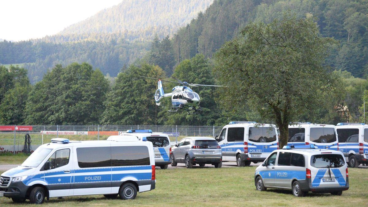 Ein Polizeihubschrauber startet von einem Sportplatz und überfliegt abgestellte Polizeifahrzeuge in Oppenau.