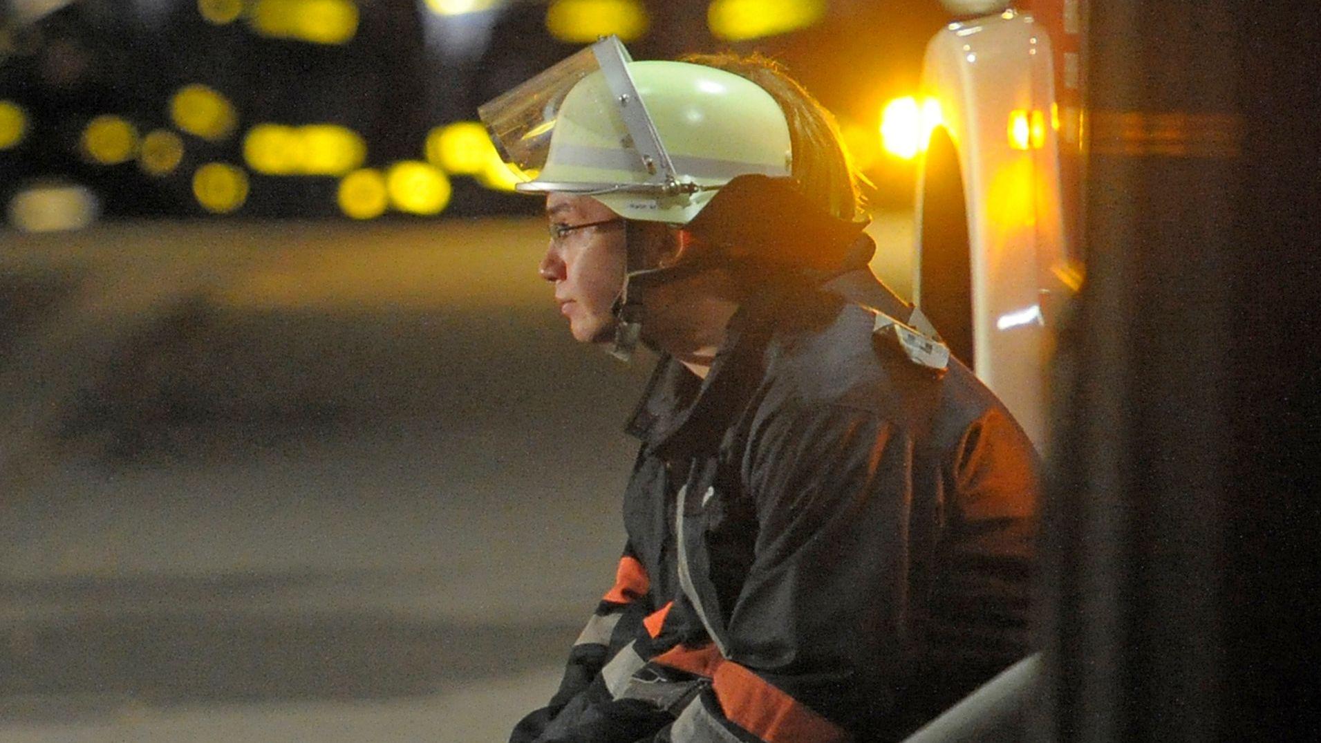 Ein Feuerwehrmann sitzt nach einem Brand in einem Wohnhaus sichtlich erschöpft an einem Einsatzfahrzeug.