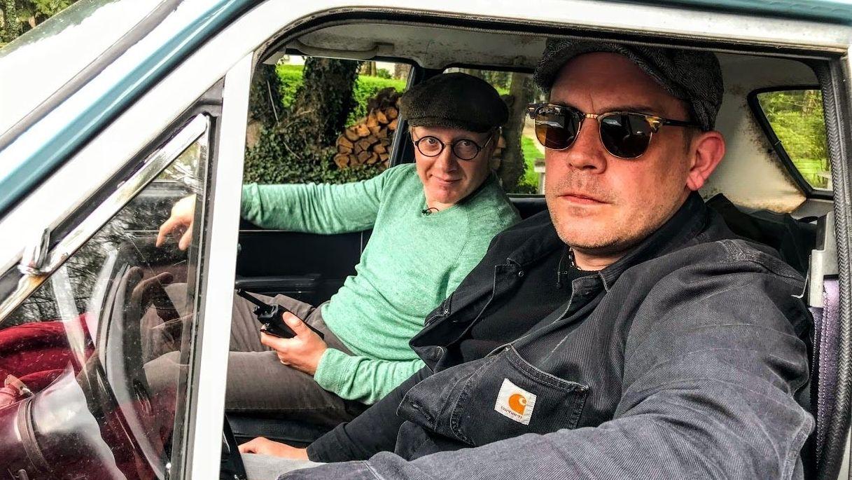 Simon Schwarz und Sebastian Bezzel schauen aus dem Seitenfenster des Autos