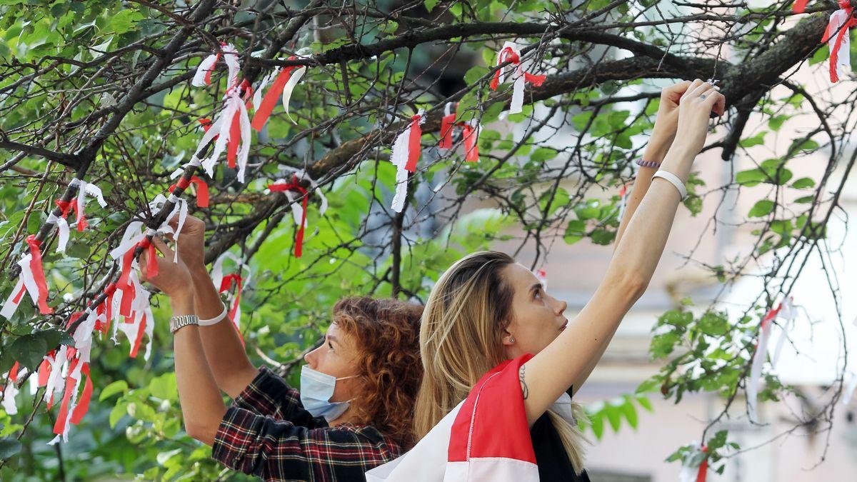 Zwei Frauen binden weiße und rote Stoffe an einen Baum.