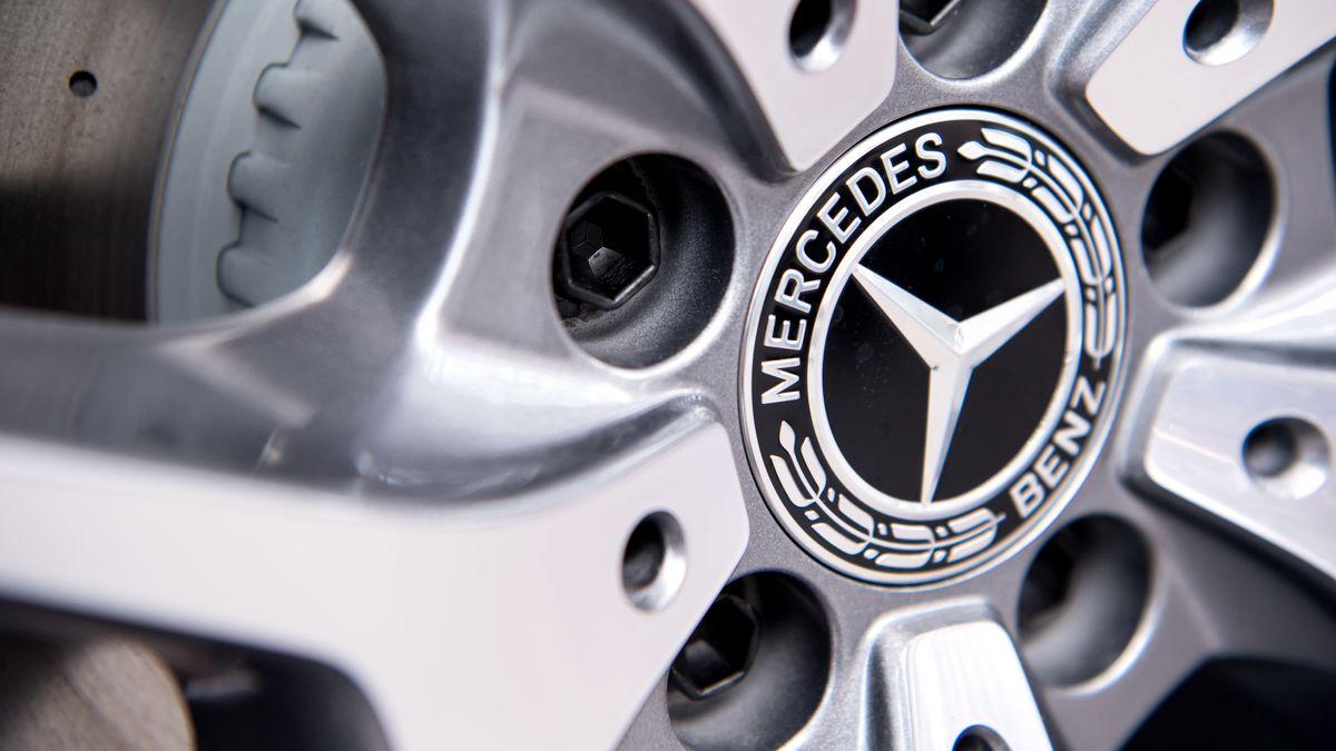 Das Logo von Mercedes Benz ist an einer Felge eines Autos zu sehen.
