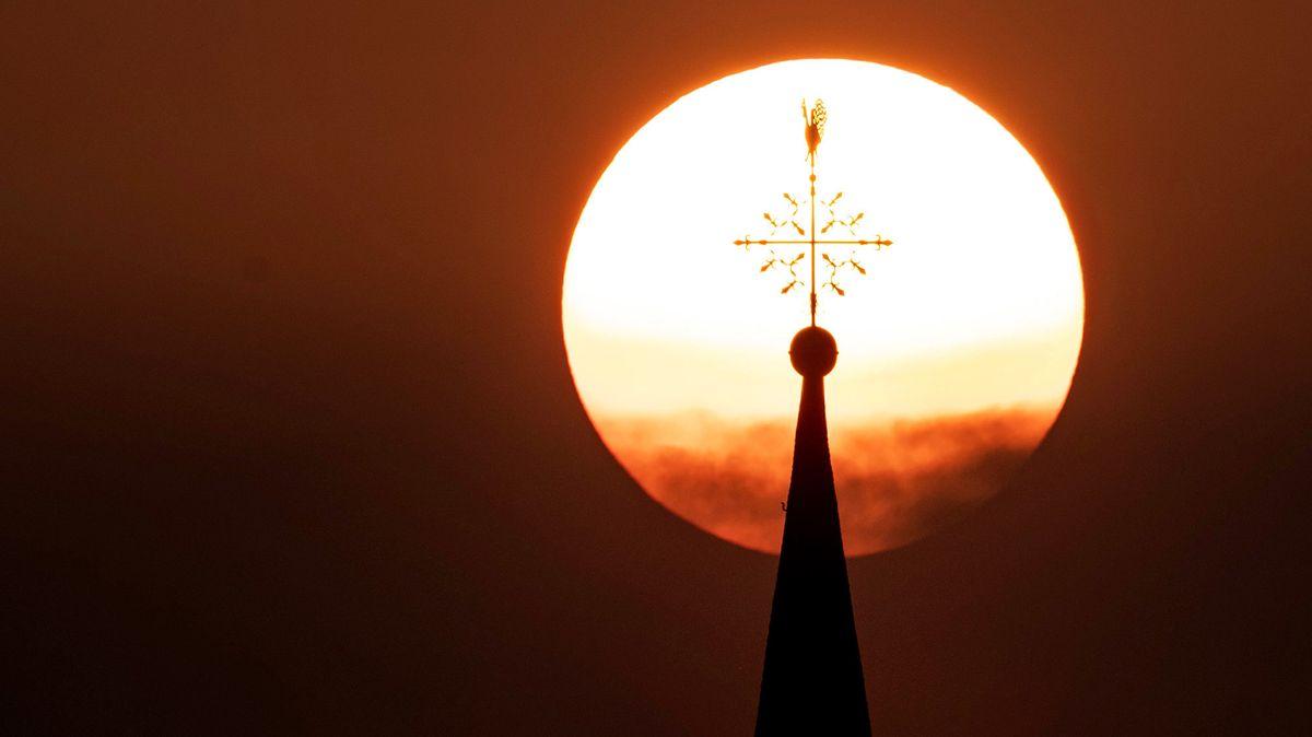 Sonne geht hinter einem Kirchturm auf.