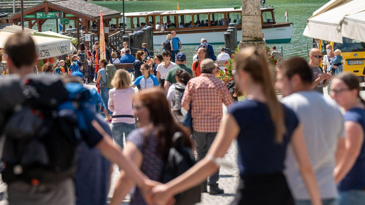 Touristen laufen eine Straße zum Königssee hinunter. In der Urlaubsregion Berchtesgadener Land herrschen erhöhte Inzidenzen.