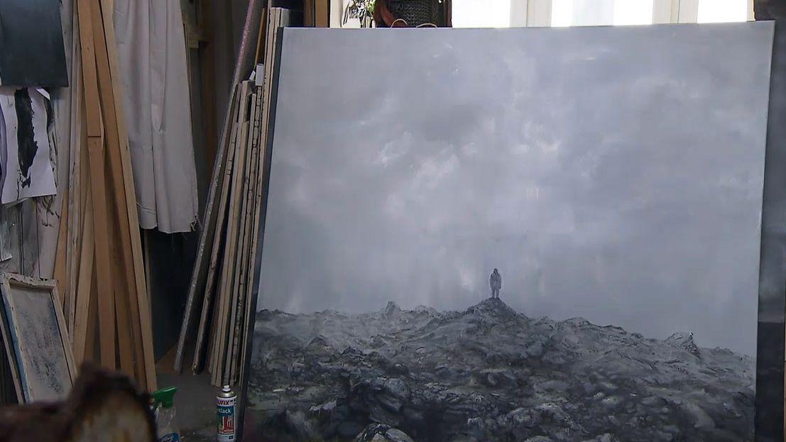 Ein Gemälde zeigt einen grauen Mann auf einem grauen Geröllhaufen.
