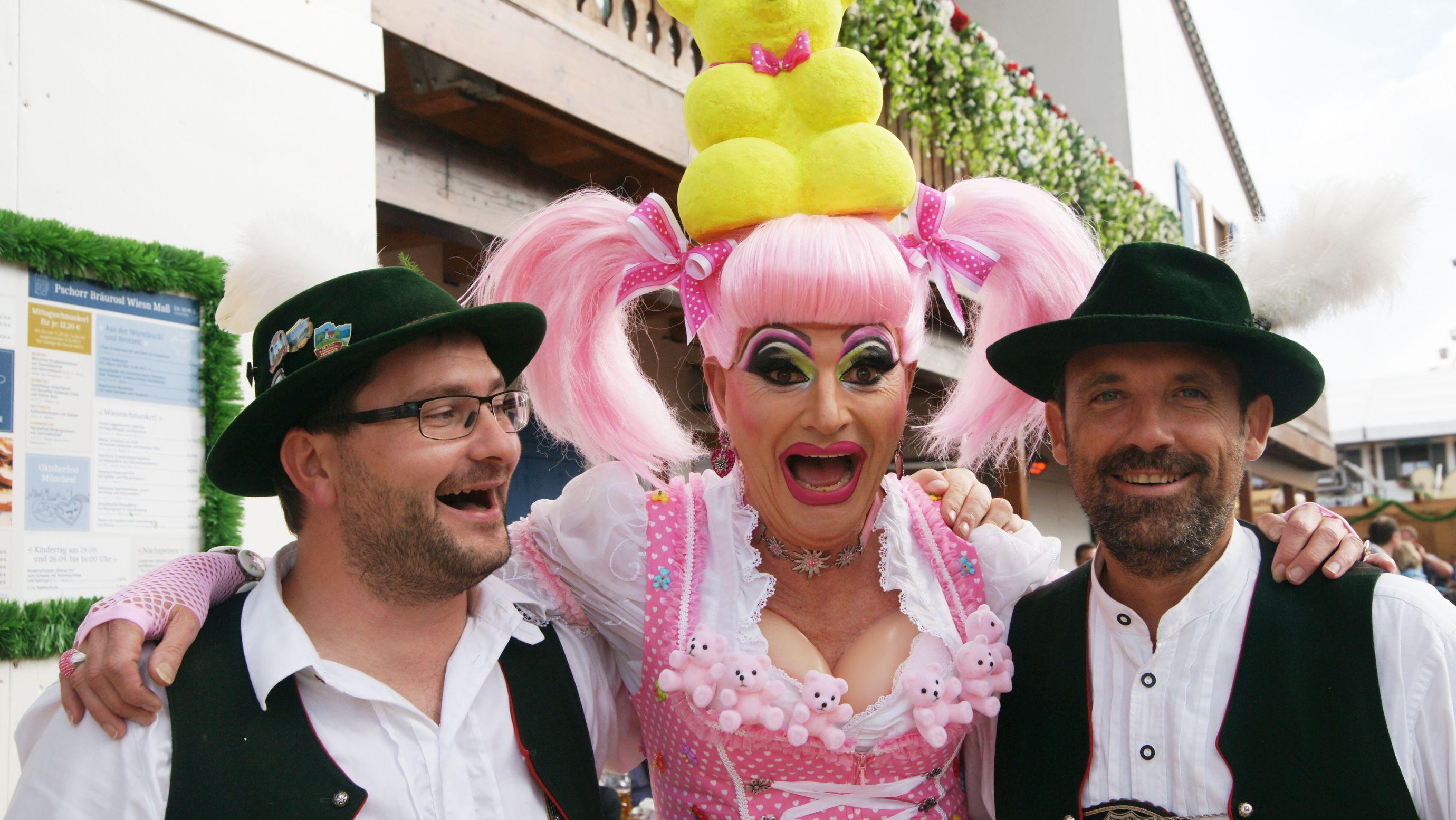 Die Drag Queen Franka posiert in pinkem Dirndl und mit Gummi-Dekolleté beim Gay-Sonntag 2017 auf dem Oktoberfest im Festzelt Bräurosl mit zwei Gästen.