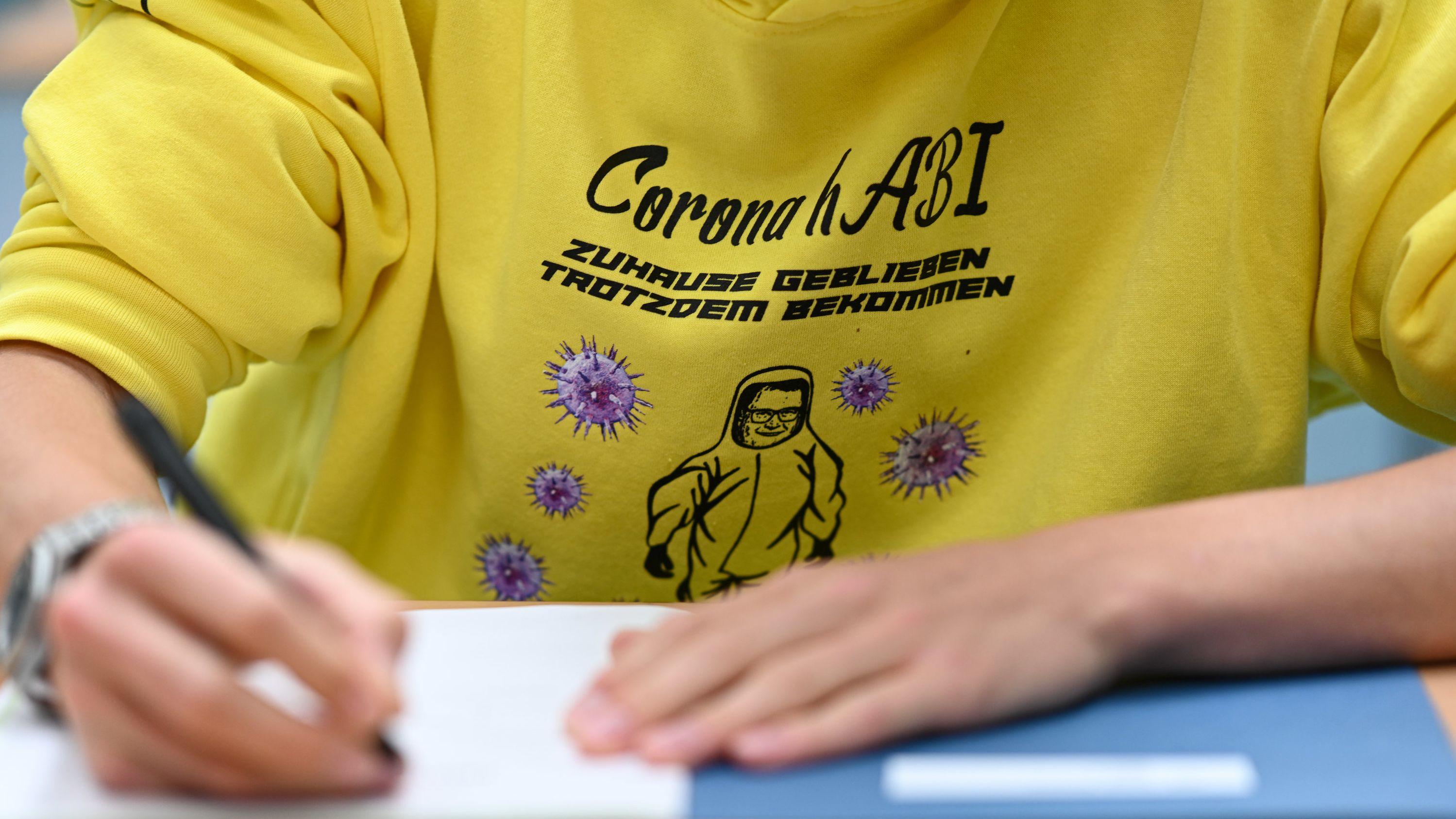 """Ein Schüler trägt einen Pullover mit der Aufschrift """"Corona-Abi"""" bei der Prüfung."""