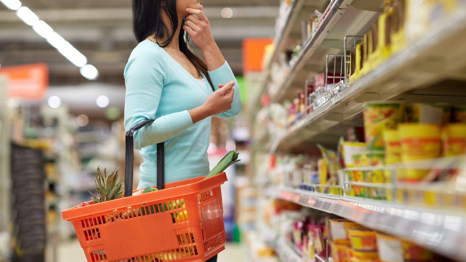 Eine Frau steht vor einem Supermarkt-Regal und sucht nach einem Produkt.