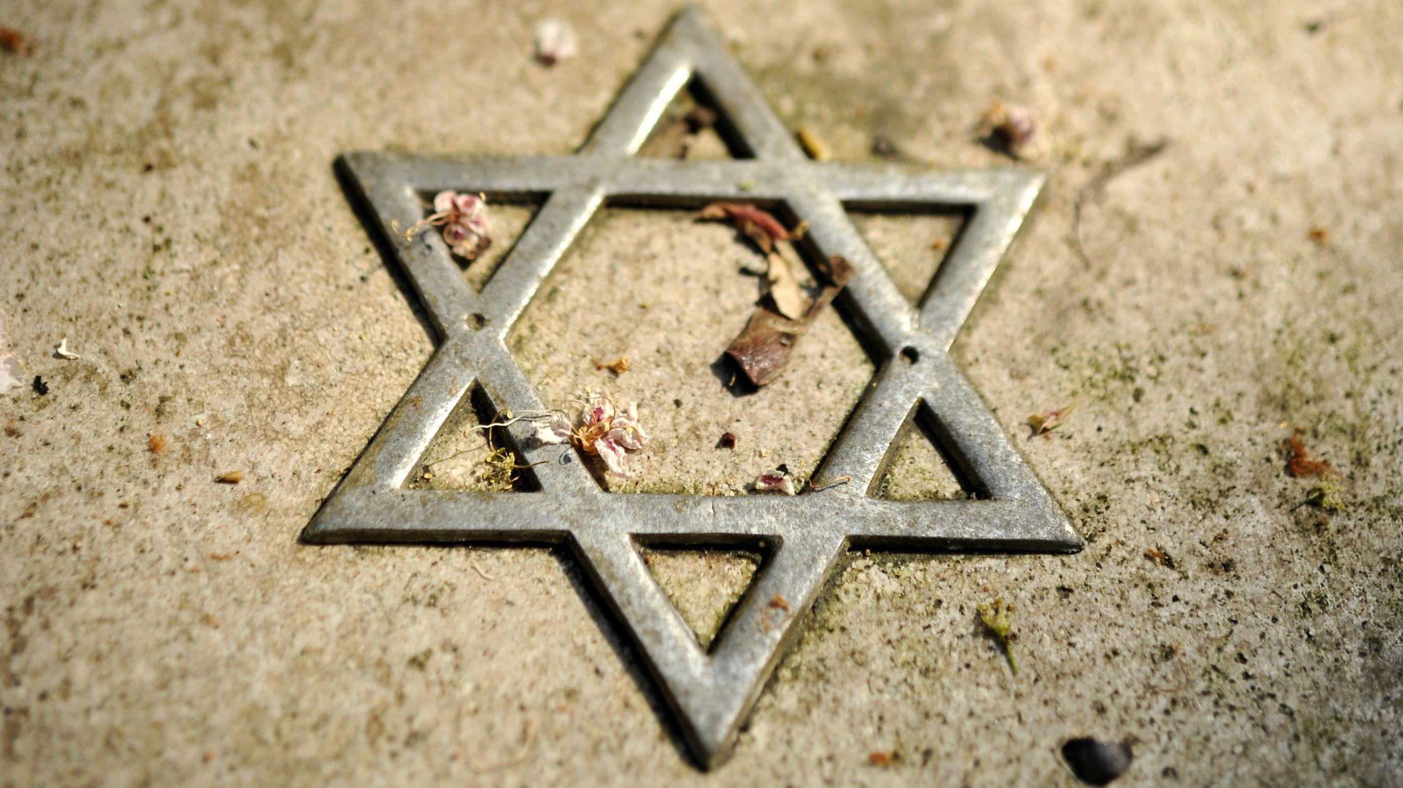 Ein Judenstern aus Metall, Laub- und Blütenreste liegen um ihn verstreut