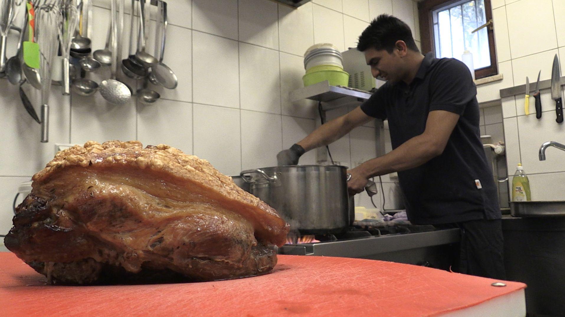 Im Vordergrund ein Schweinebraten, im Hintergrund Koch Sajid Ali.