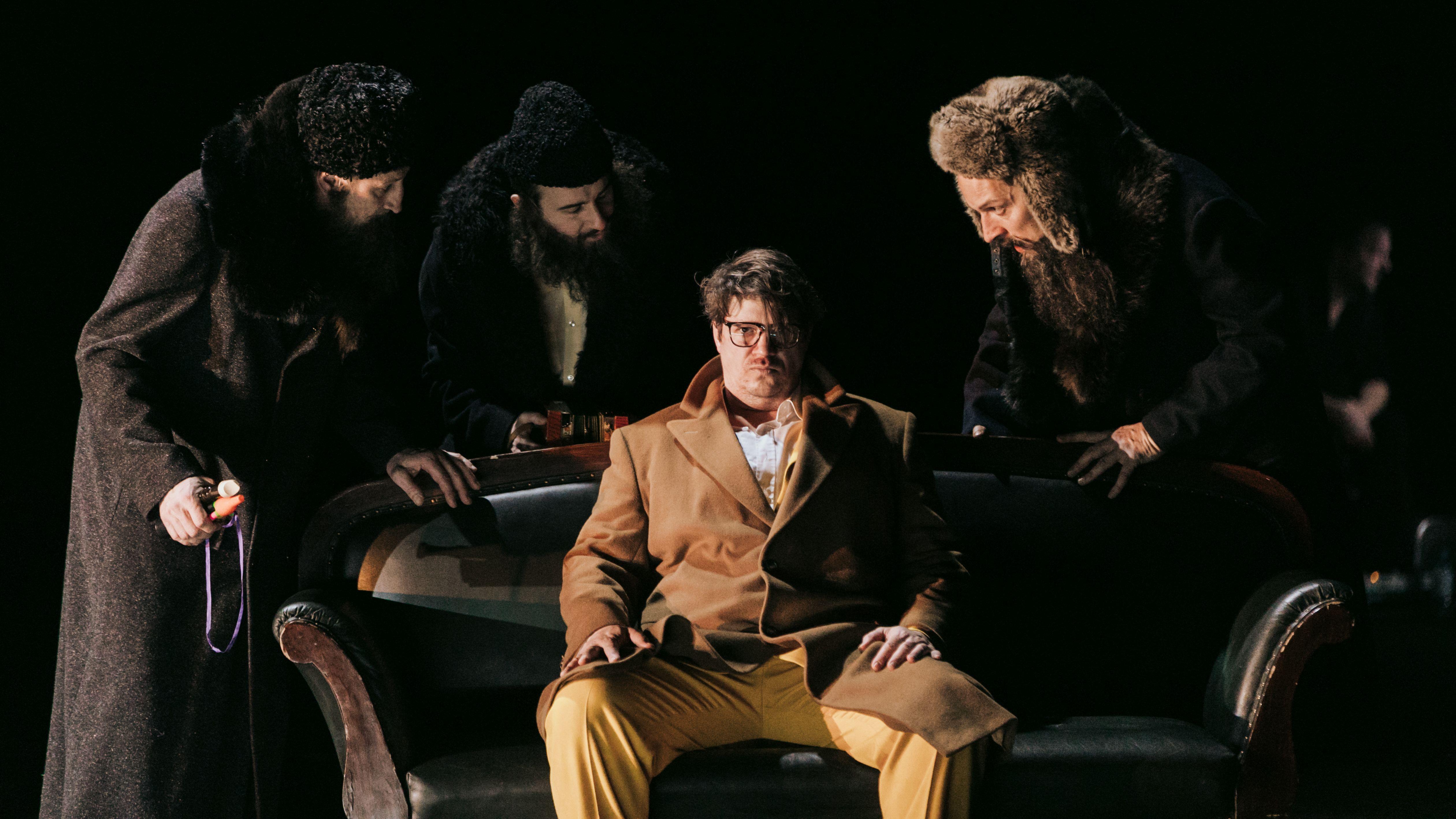 Thomas Frank in der Rolle des Ferdinand Krutzler sitzt im Mantel auf einem Sofa, um ihn herum stehen drei Männer in Winterkleidung