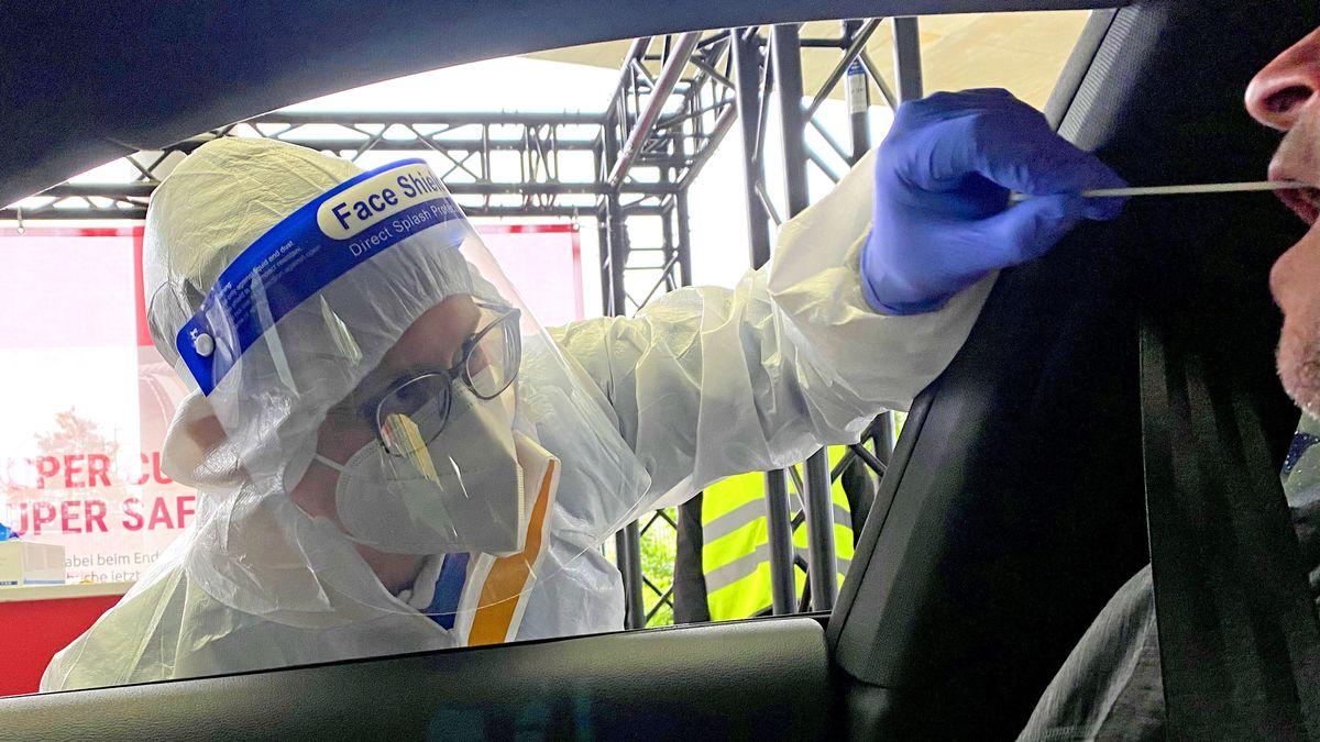 Medizinisches Personal nimmt einen Abstrich von einer Person an einer Drive-Through-Teststation