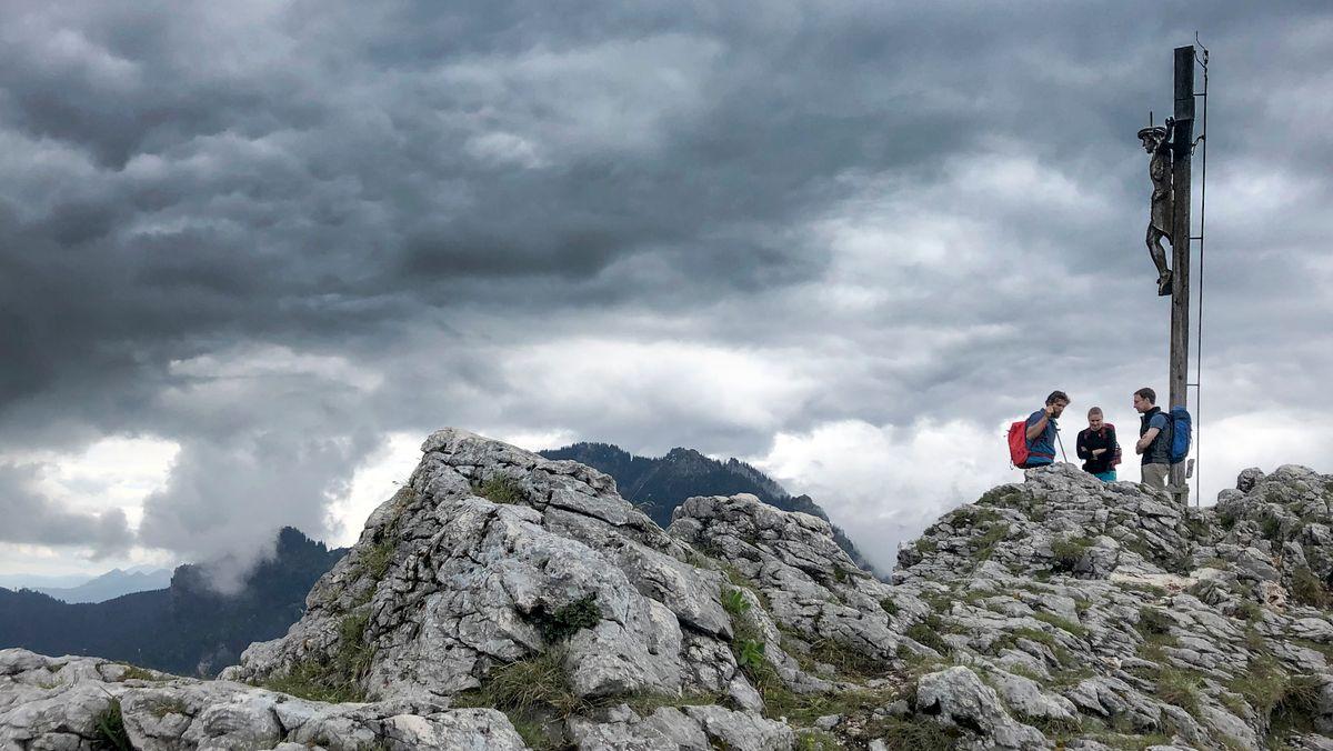 Drei Wanderer stehen neben einem Gipfelkreuz