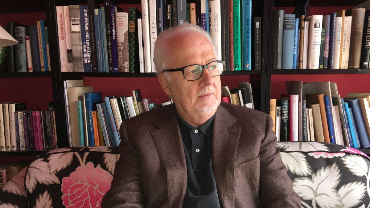 Jens Malte Fischer sitzt vor seinem Bücherregal.