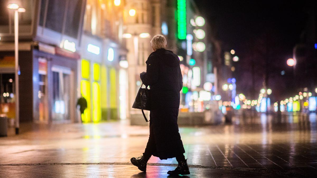 Ein Frau spaziert über einen leeren Marktplatz.