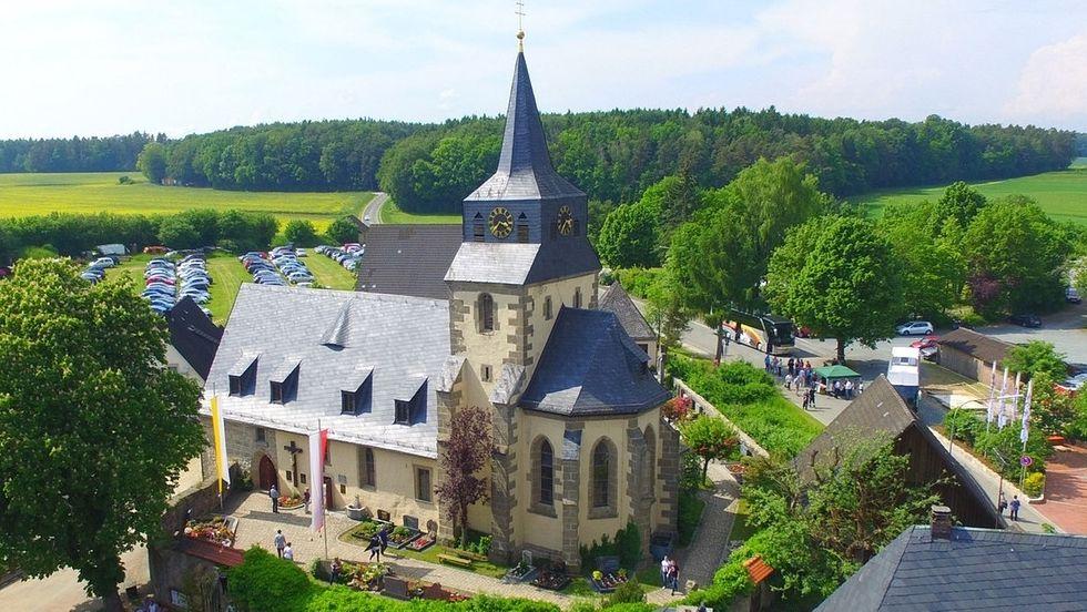 Die Kirche von Modschiedel mit seinem spitzen Turm aus der Vogelperspektive betrachtet, im Hintergrund grüne Wiesen und Wälder.