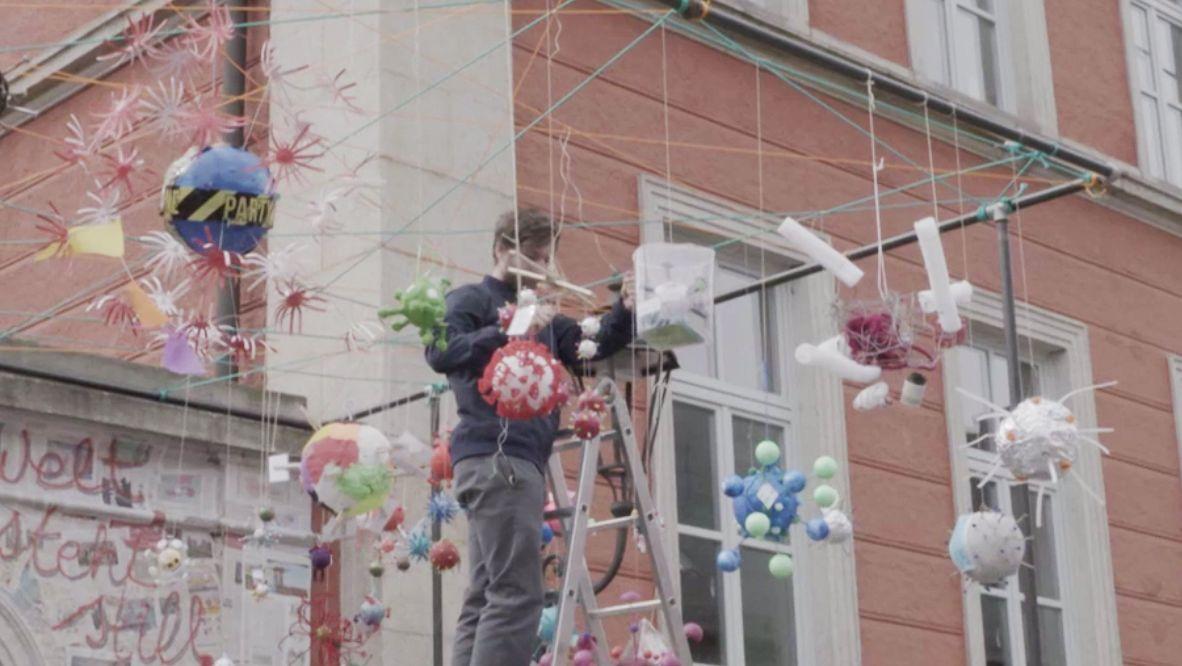 Schüler des Luisen-Gymnasiums verzierten ihren Brunnen mit gebastelten Viren. Schüler steht auf der Leiter und hängt die bunten Kunstwerke auf.