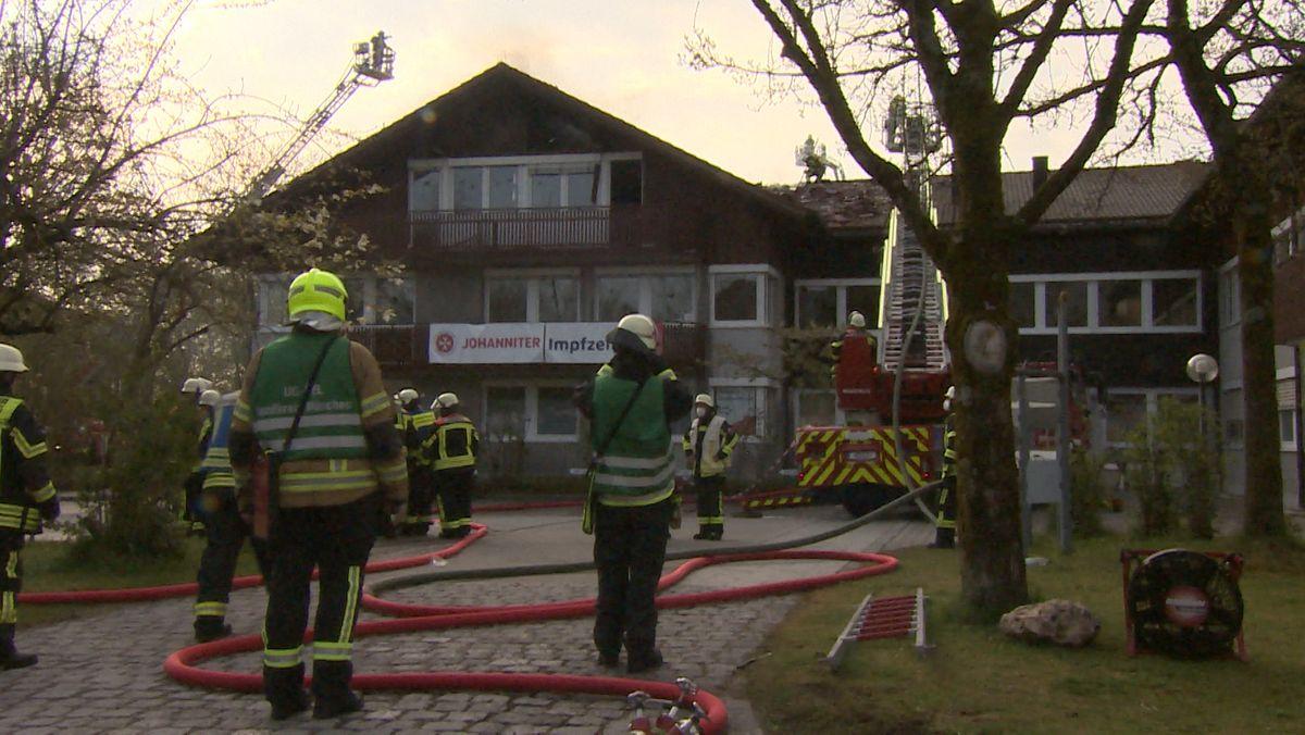 Feuerwehrmänner stehen vor Impfzentrum in Oberhaching