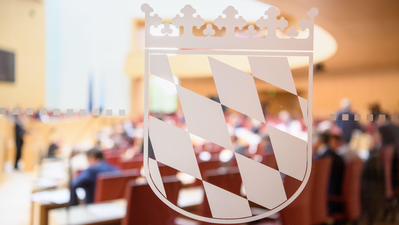 Blick durch die Fensterscheibe am Plenarsaal im Landtag mit dem Wappen von Bayern während einer Sitzung (Archivbild Juni 2017).