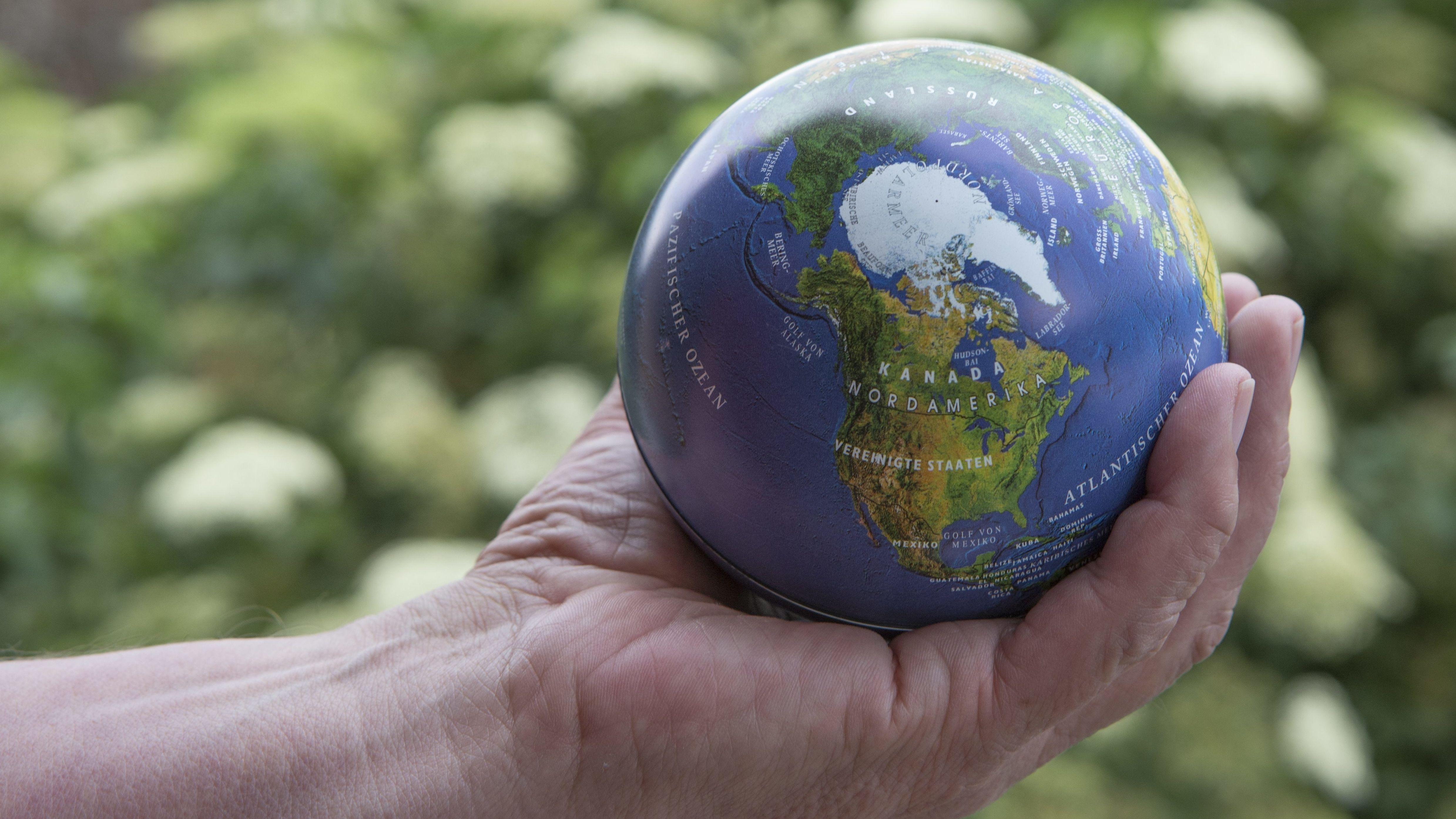Eine Hand hält eine Kugel in Gestalt der Erde.