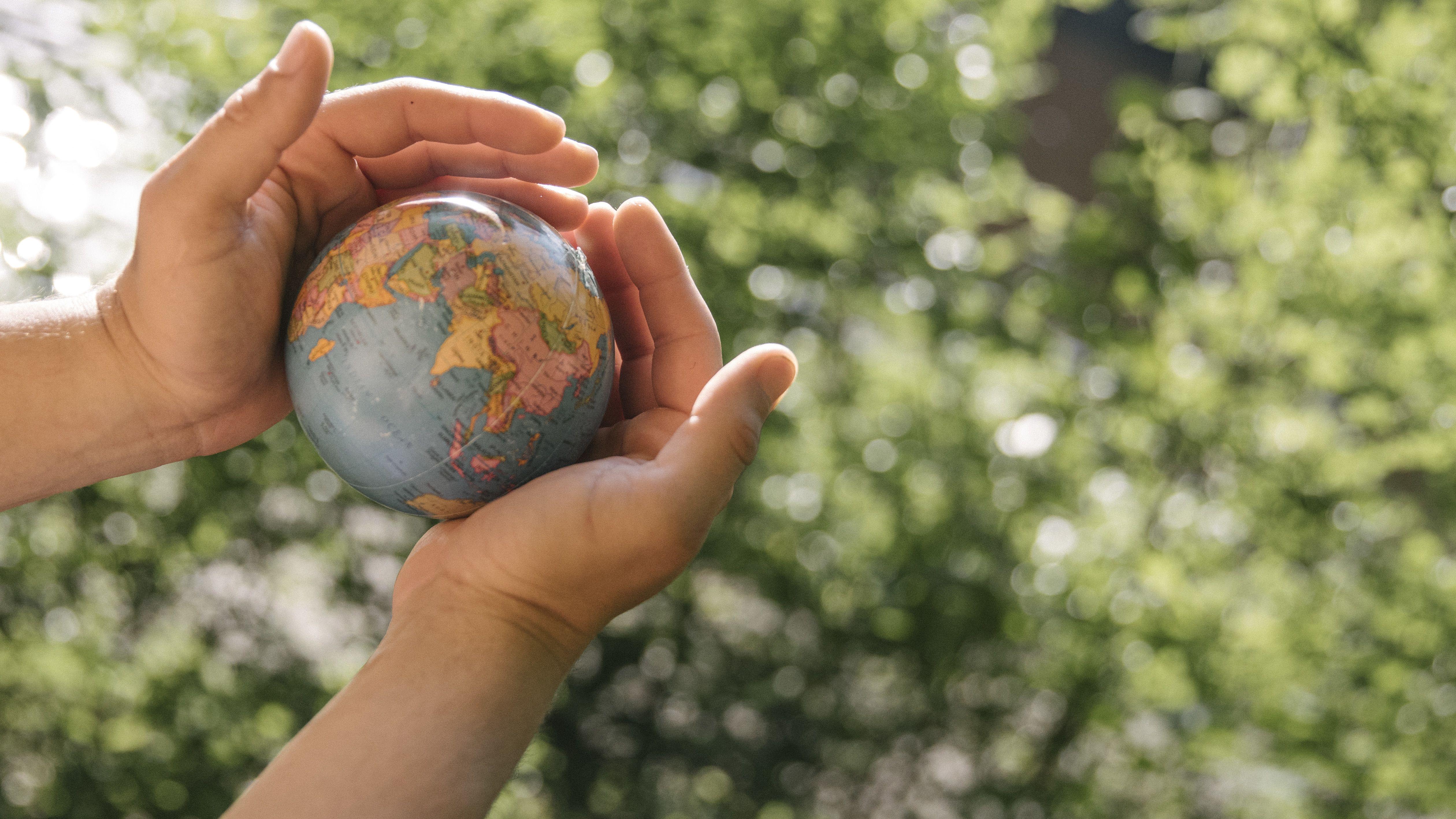 Ein Mann hält die Weltkugel in seinen Händen