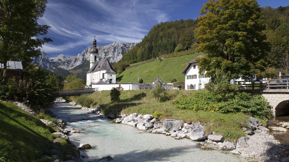 Kirche in Ramsau in malerischer Kulisse mit Bach im Vordergrund und Bergen im Hintergrund