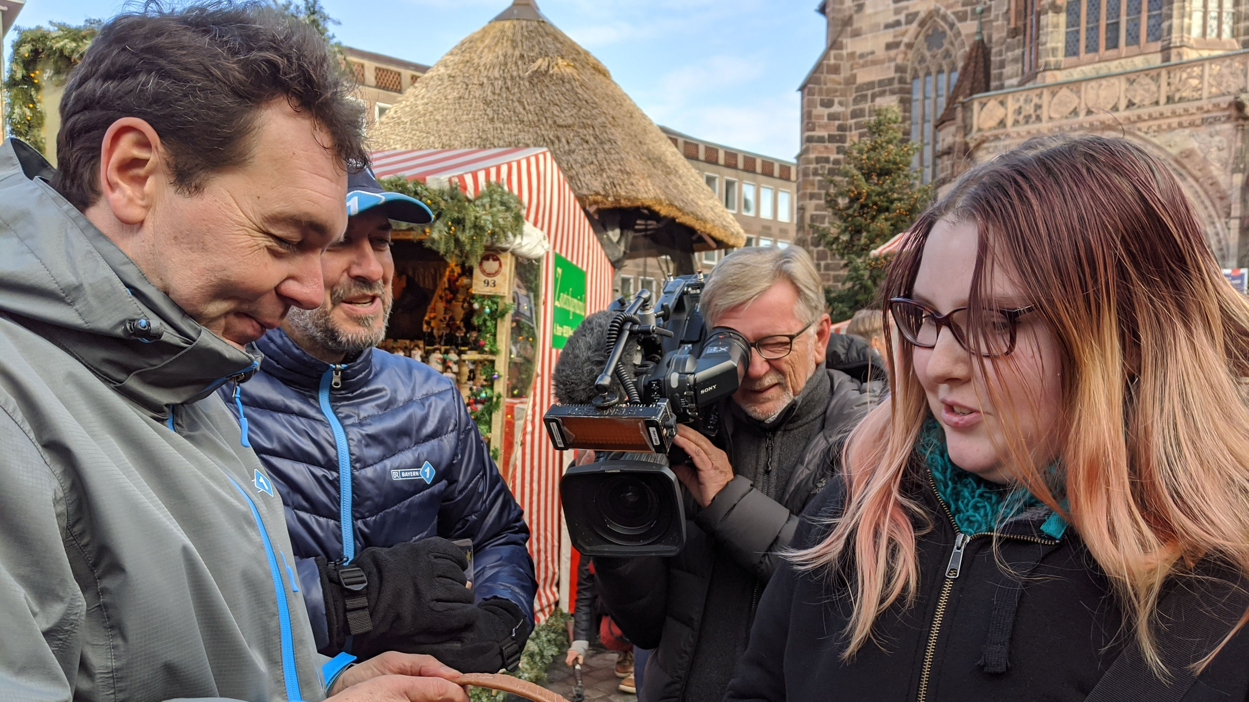 Jürgen Lassauer und Stefan Strasser im Gespräch mit einer Passantin, im Hintergrund filmt ein Kameramann