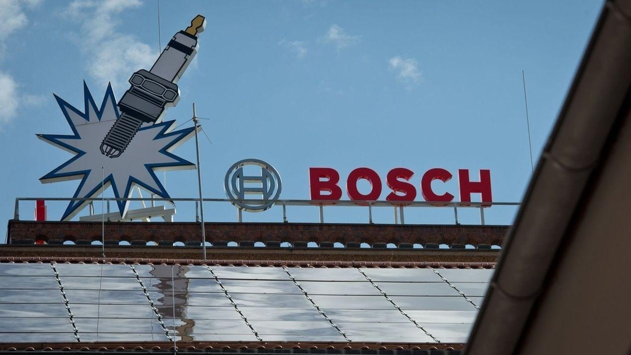 """Auf dem Dach des Werkes in Bamberg steht in roten Buchstaben """"Bosch"""", daneben eine große stilisierte Zündkerze."""