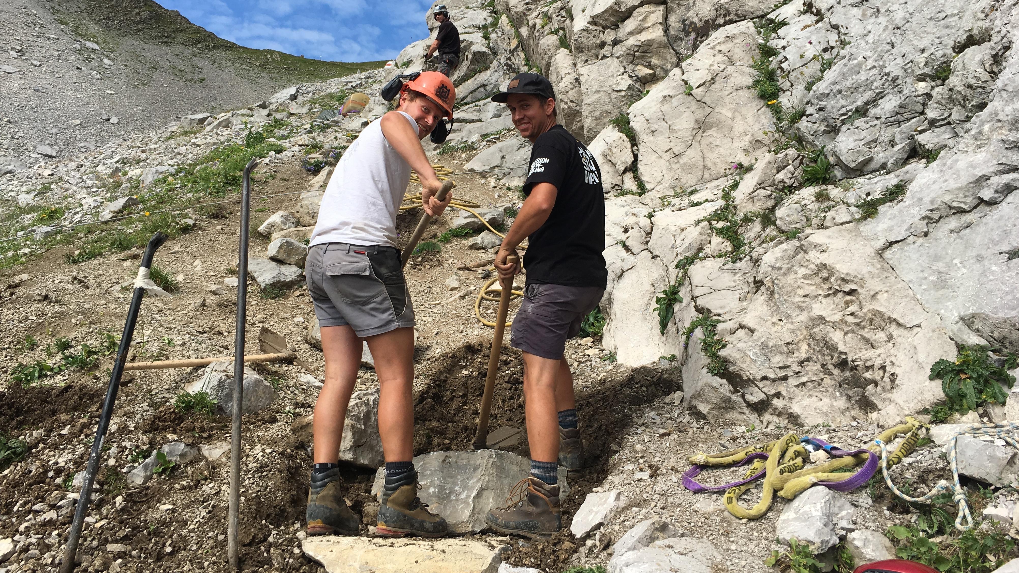 Zwei Männer in kurzen Hosen und Bergschuhen graben auf einem steilen Weg, um große Steine zu einer Treppe aufzustapeln