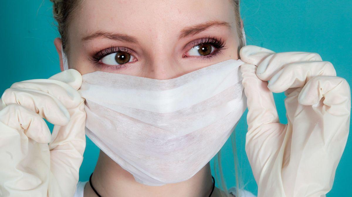 Frau mit Mundschutz und Gummihandschuhen