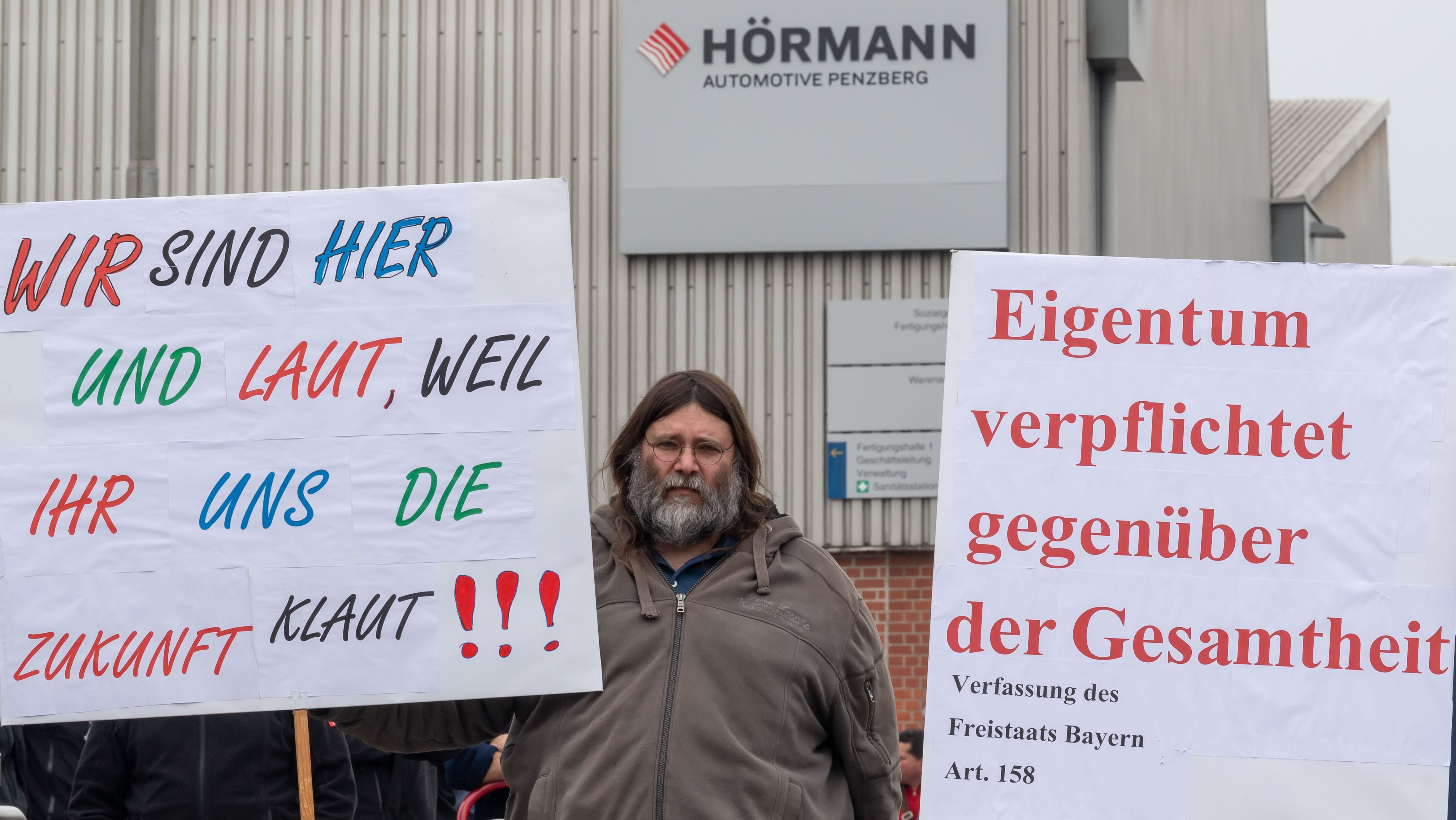 11.04.2019, Bayern, Penzberg: Mitarbeiter der Firma Hörmann - Automotive demonstrieren am Werkseingang mit Plakaten gegen die Schließung ihres Standortes. Das Werk Penzberg von Automotive Hörmann, der größte Geschäftsbereich der Hörmann Industries, soll bis zum 30. Juni 2020 geschlossen werden.