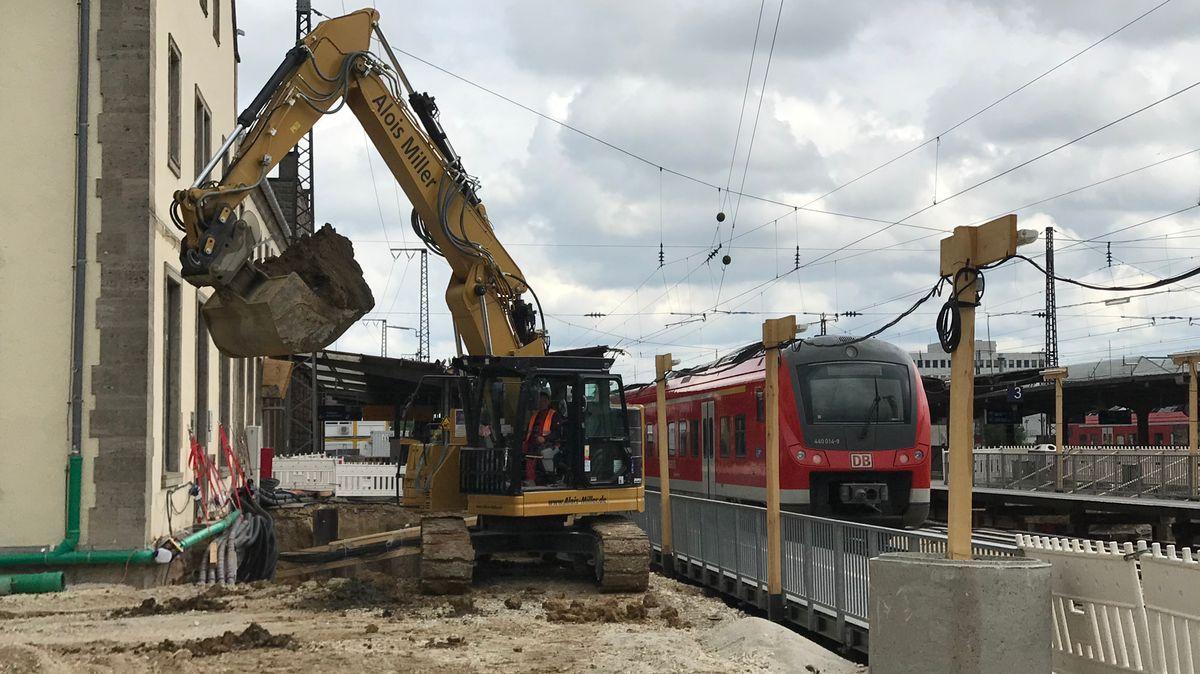 Ein gelber Bagger mit Erde in der Schaufel, durch Gitterzaun von Bahnsteig und roter Regionalbahn getrennt.