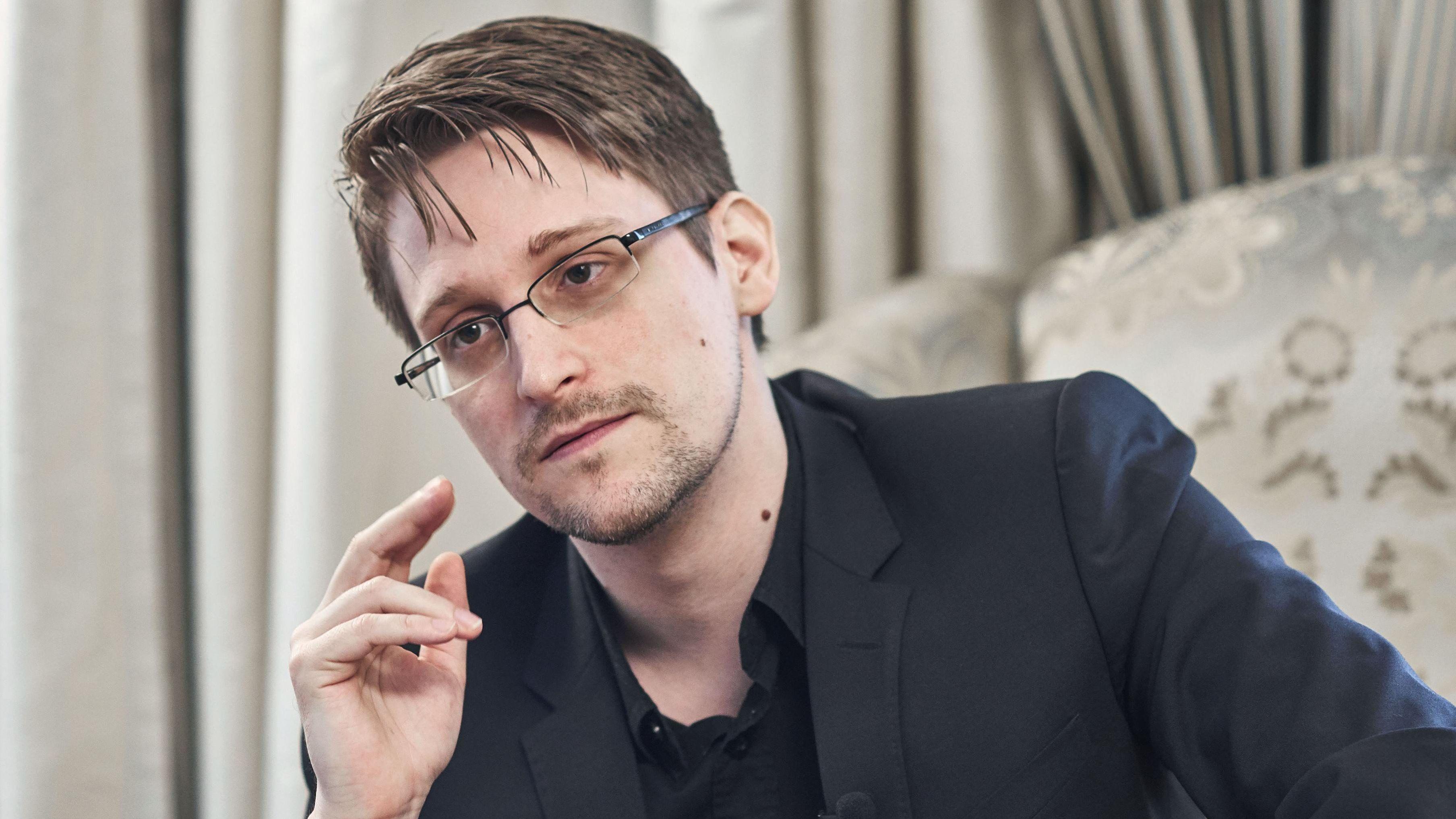 Edward Snowden sitzt in einem Sessel, die schweren Vorhänge hinter ihm sind zugezogen