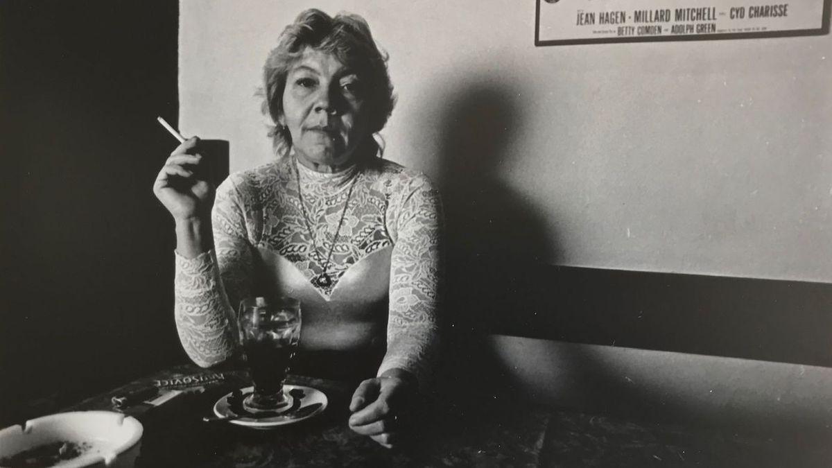 Eine Frau sitzt an einem Tisch und raucht eine Zigarette.