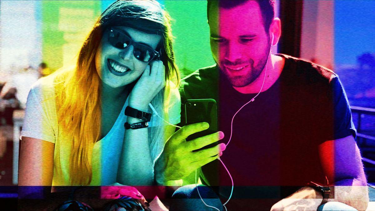 Ein junger Mann und eine junge Frau teilen sich die Ohrstecker eines Handys und freuen sich