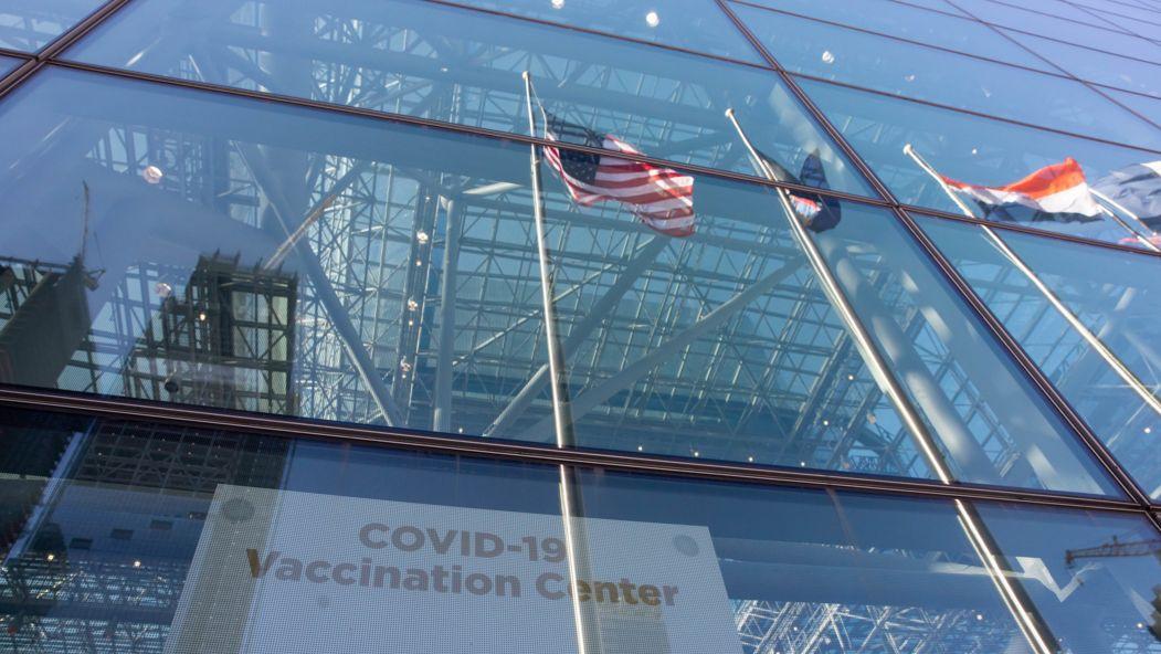 New York: Fahnen spiegeln sich im Fenster eines COVID-19-Impfzentrums