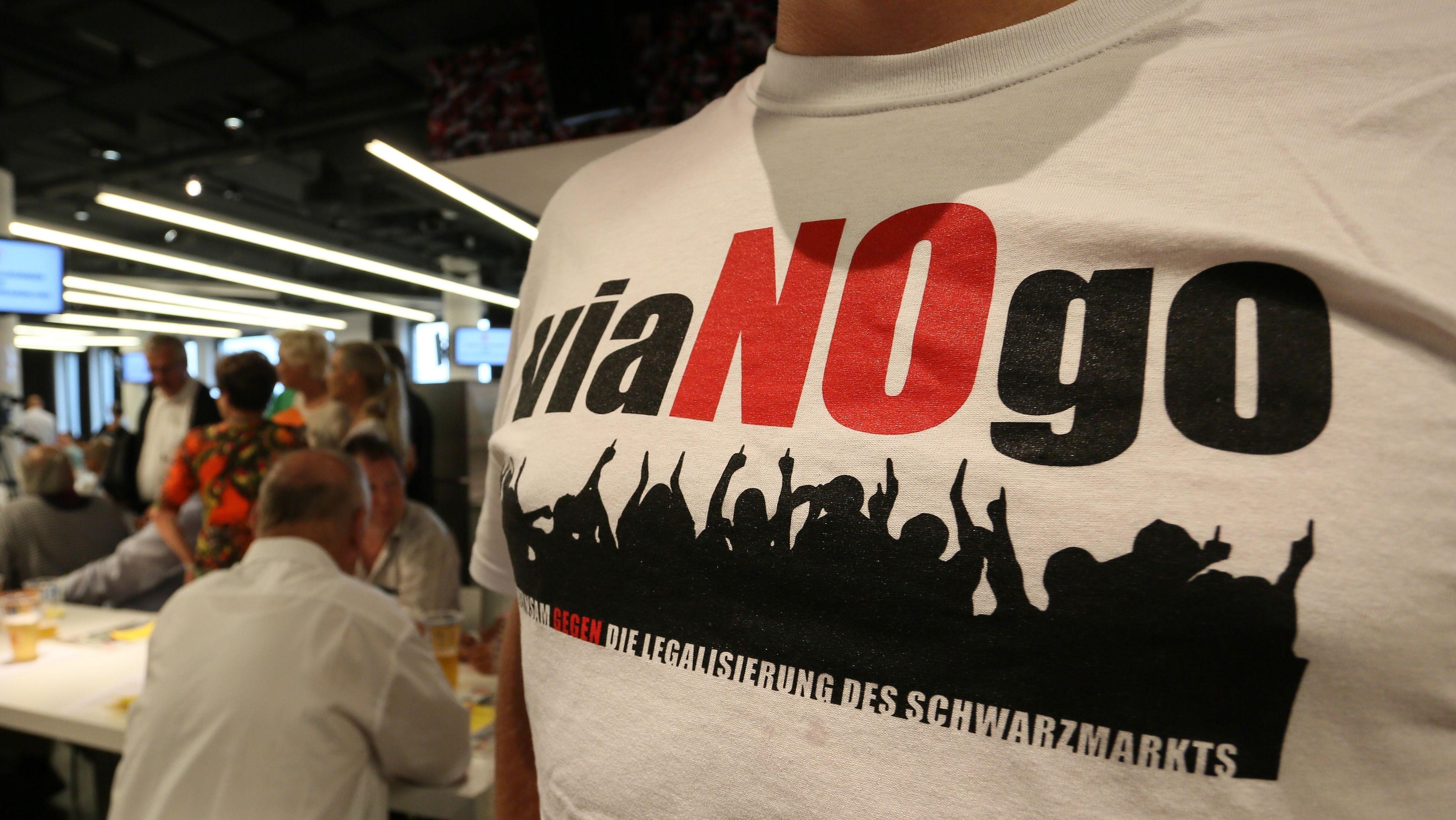 """viagogo-Gegner mit T-shirt-Aufdruck """"viaNOgo"""" während der Mitgliederversammlung des FC Augsburg"""