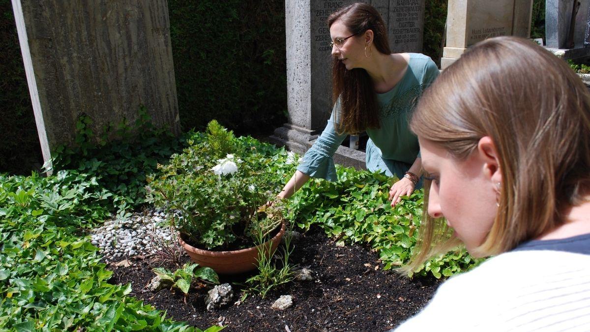 Die Hochzeitsplanerinnen Meike Höhne und Christine Reim arbeiten an einem Grab.