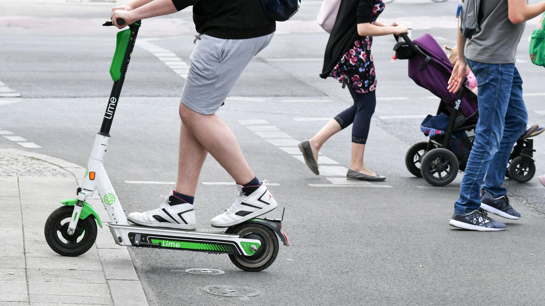 Archivbild: Ein E-Tretroller und Fußgänger im Straßenverkehr.
