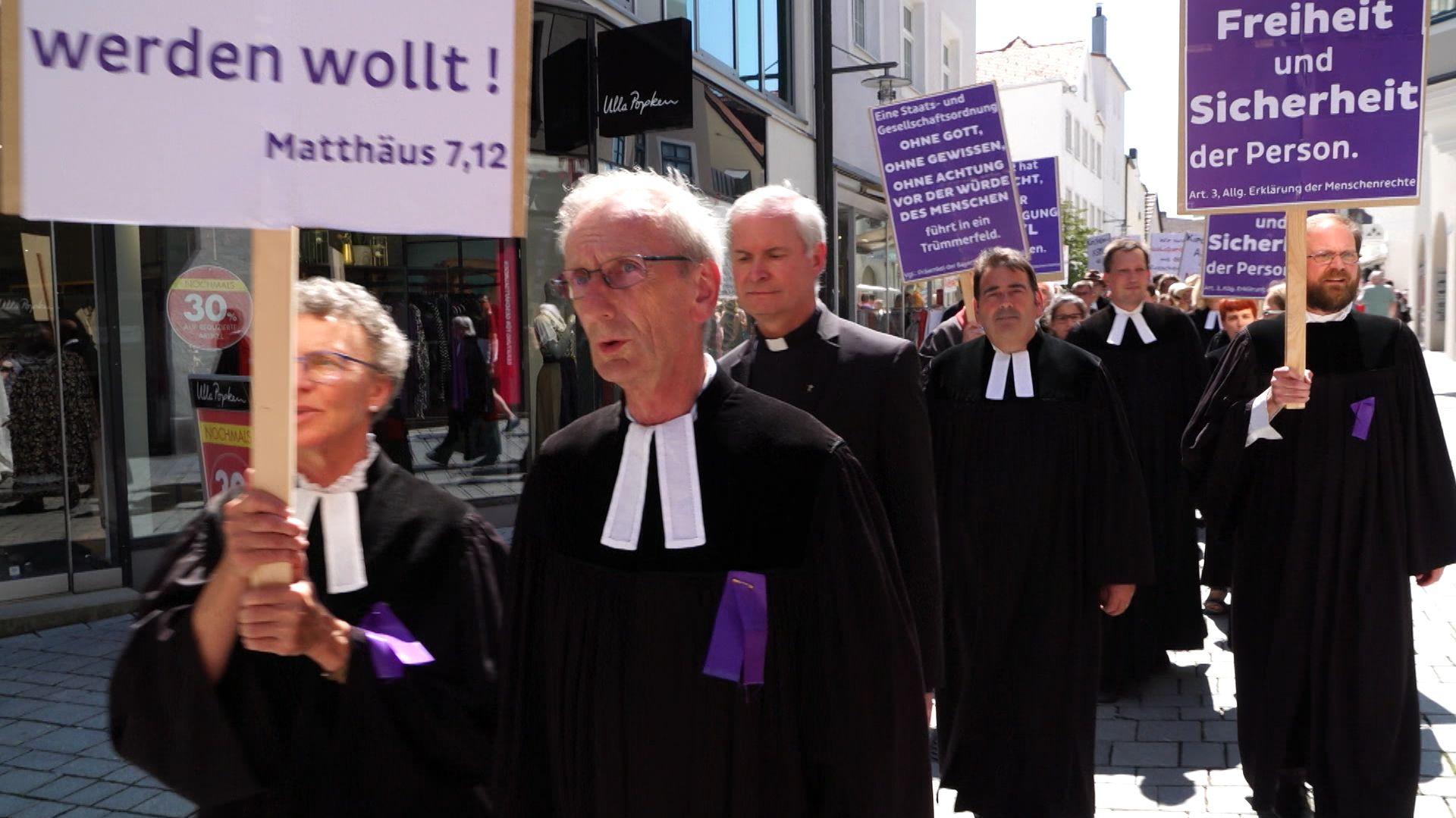 Kirchenvertreter gehen mit Plakaten in der Hand durch Kempten. Hinter ihnen rund 250 Menschen, die sich am Schweigemarsch beteiligt haben.