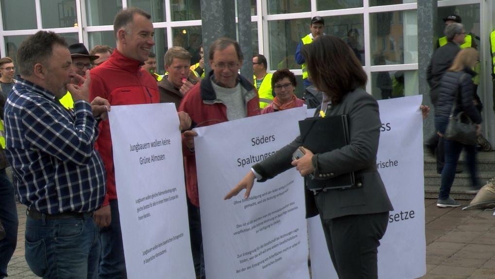 Vor der Stadthalle Kulmbach stehen mehrere Bauern mit Plakaten. Landwirtschaftsministerin Kaniber schaut sich die Plakate an.