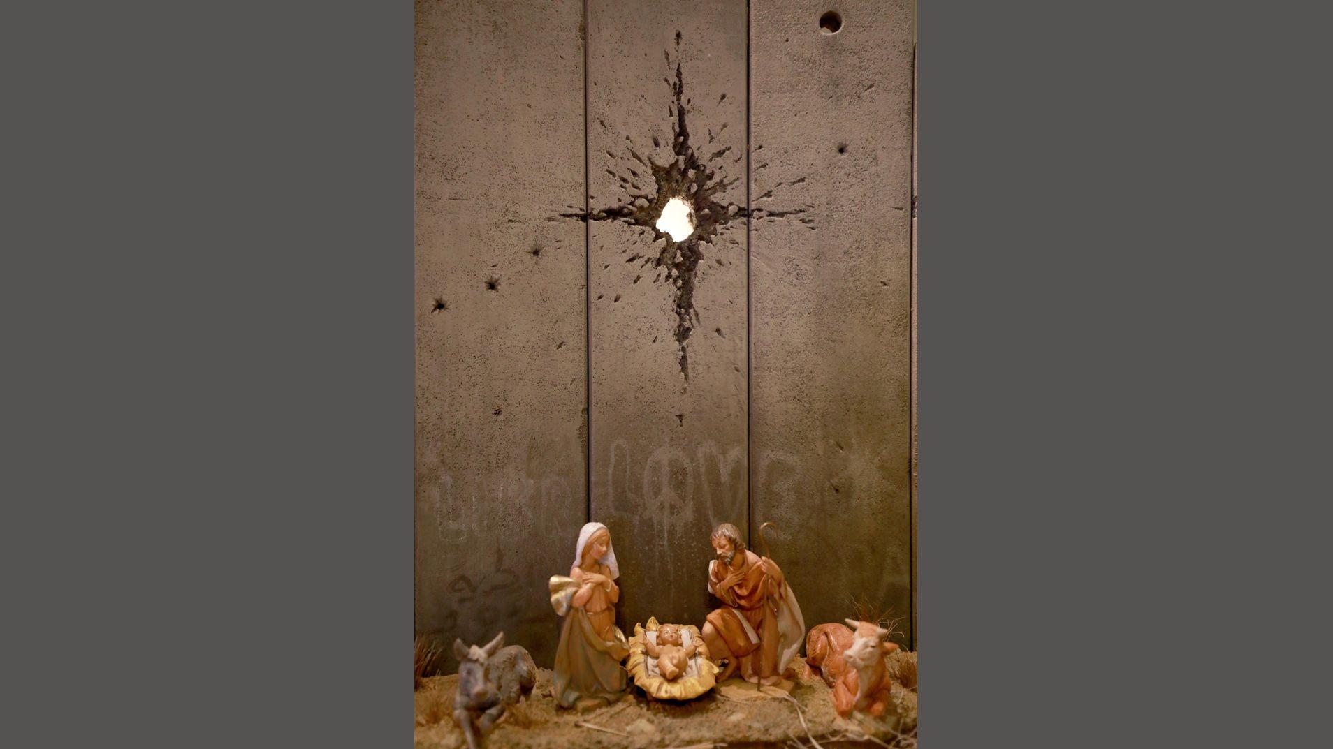 Maria und Josef, Ochs und Hirte und das Jesuskind vor einer durchschossenen Beton Mauer von Banksy
