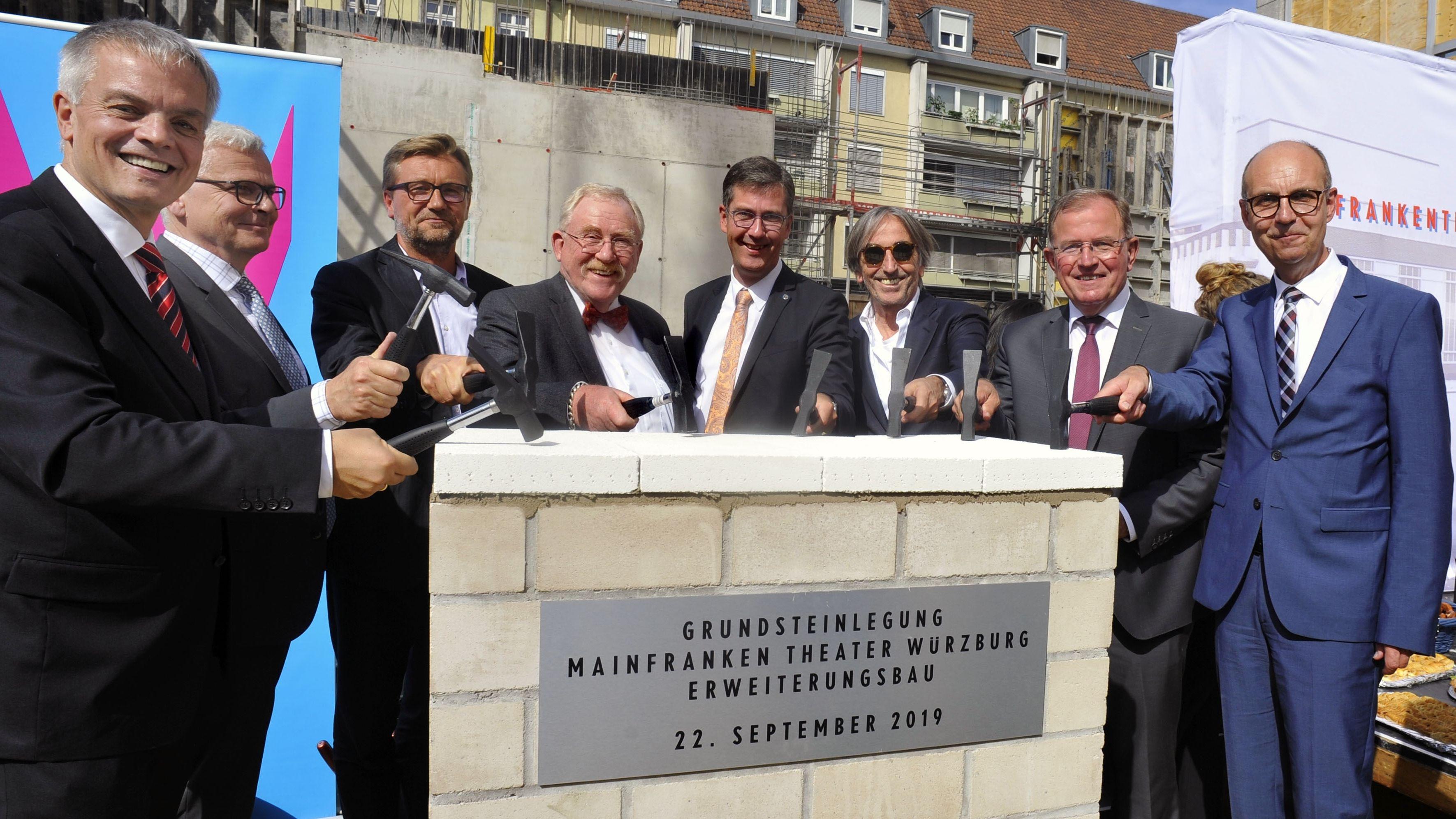 Mehrere Männer stehen bei einer Grundsteinlegung am Mainfranken Theater Würzburg um eine Säule herum und haben Hammer in den Händen.