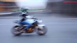 Ein Mann auf einem Motorrad - Aufnahme mit etwas längerer Belichtungszeit    Bild:picture alliance / Wolfram Steinberg