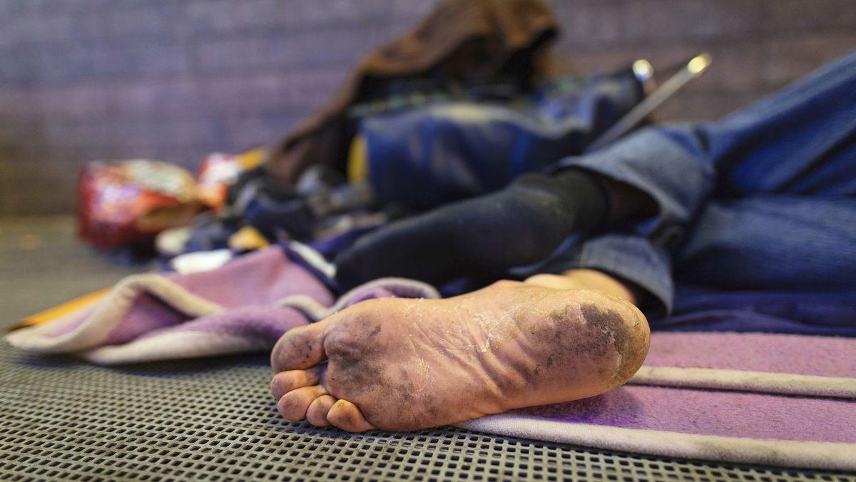 Ein Obdachloser liegt barfuß auf einer Decke im öffentlichen Raum.