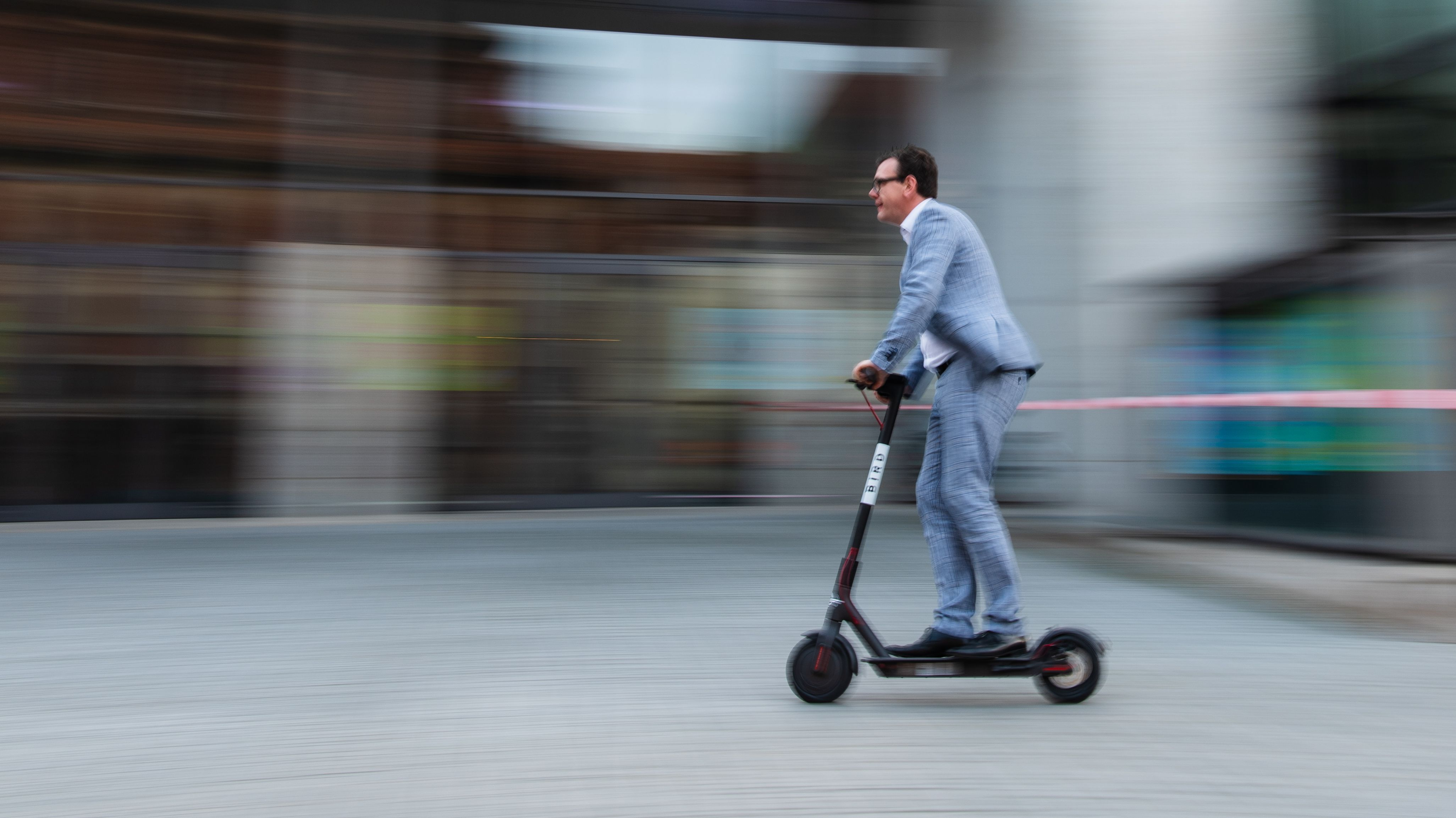 Ein Mann fährt mit einem Elektroroller durch die Innenstadt.