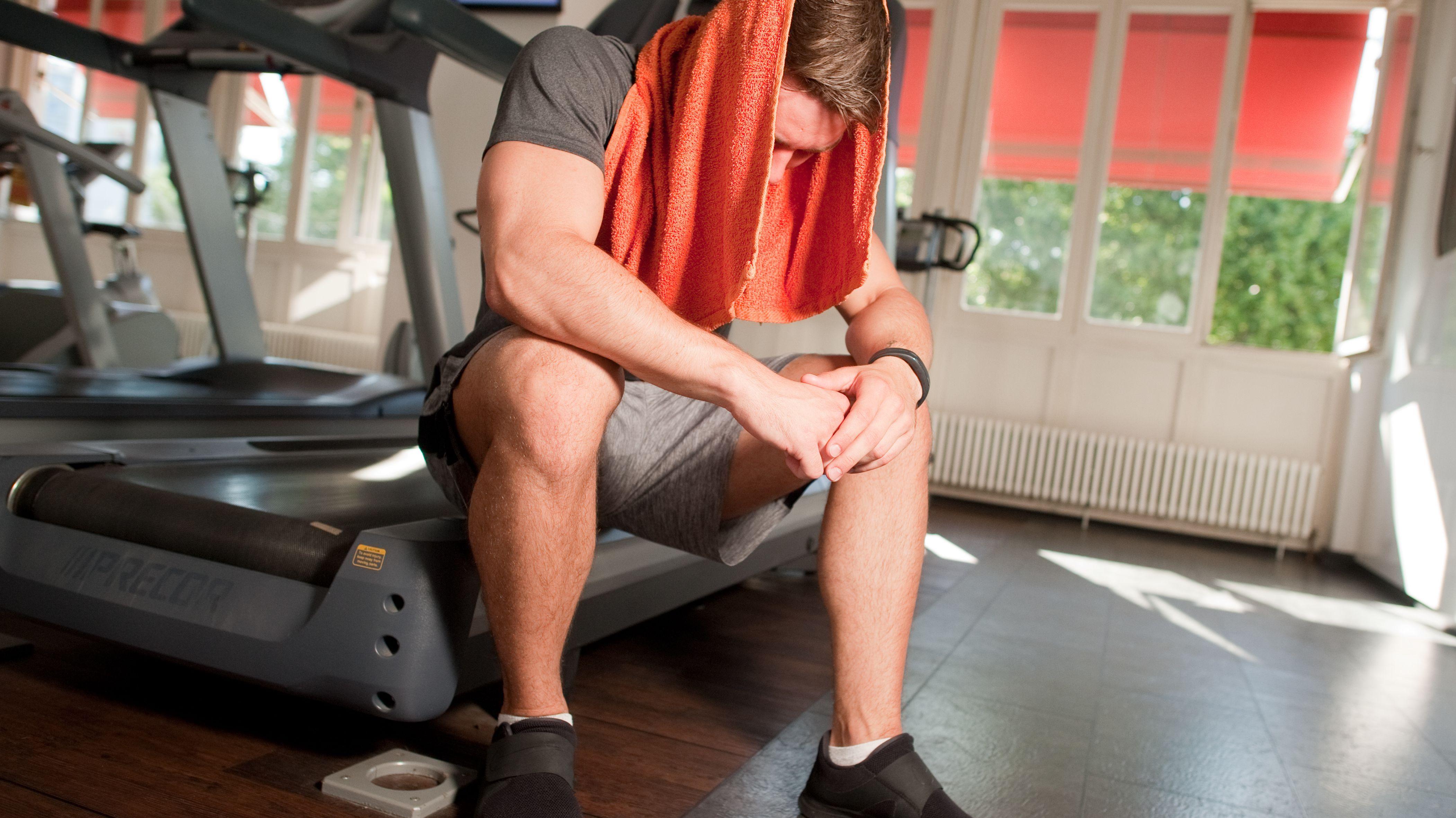Ein Sportler sitzt nach dem Training erschöpft mit einem Handtuch auf seinem Kopf auf einem Laufband