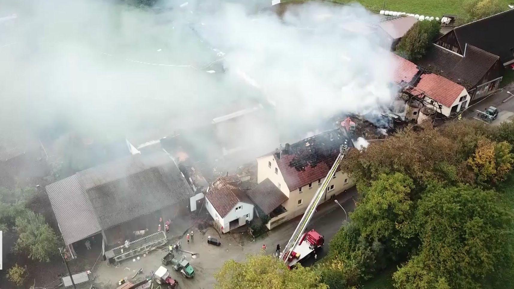 Luftaufnahme des niedergebrannten Bauernhofs, eine dicke Rauchsäule steigt aus der Mitte auf.