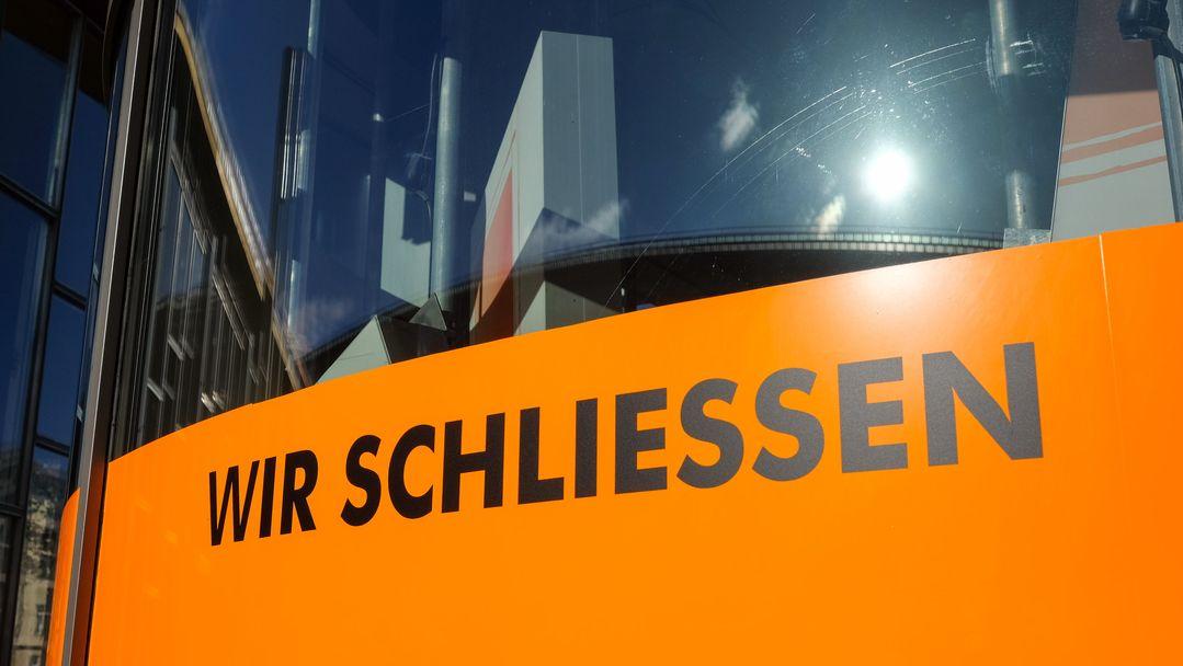 """""""Wir schliessen"""" steht in schwarzer Schrift auf orangenem Hintergrund im Schaufenster eines Geschäfts."""