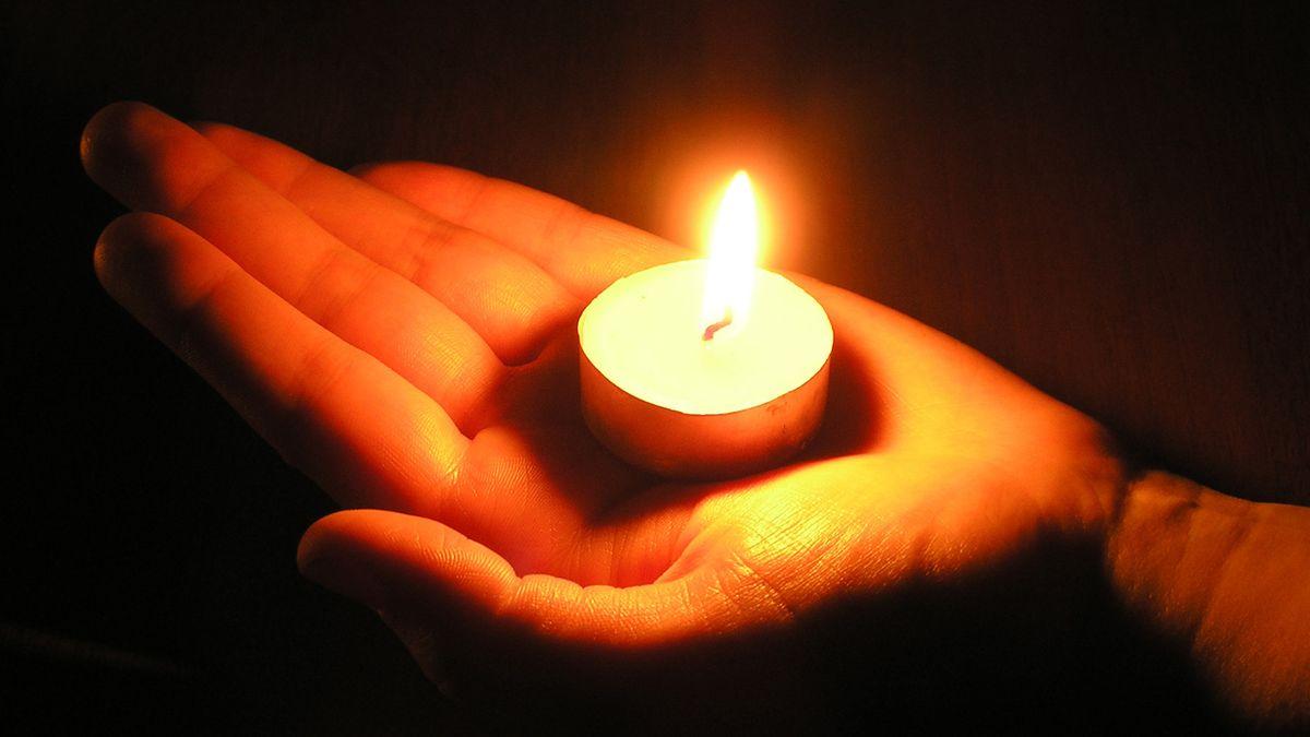 Brennende Kerze in einer Hand