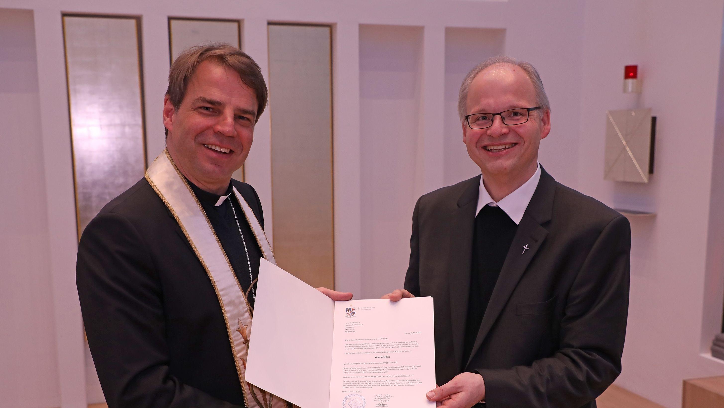 Bischof Stefan Oster überreicht Domkapitular Josef Ederer die Ernennungsurkunde zum Generalvikar
